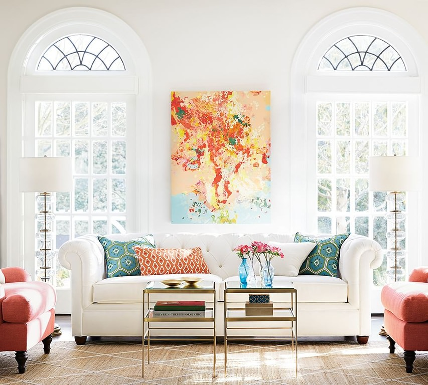 A magnificently designed living room with shades of blue, red and orange. The white sofa would blend into the white wall behind without the emphasis provided by the colorful patterned throw pillows and wall painting.