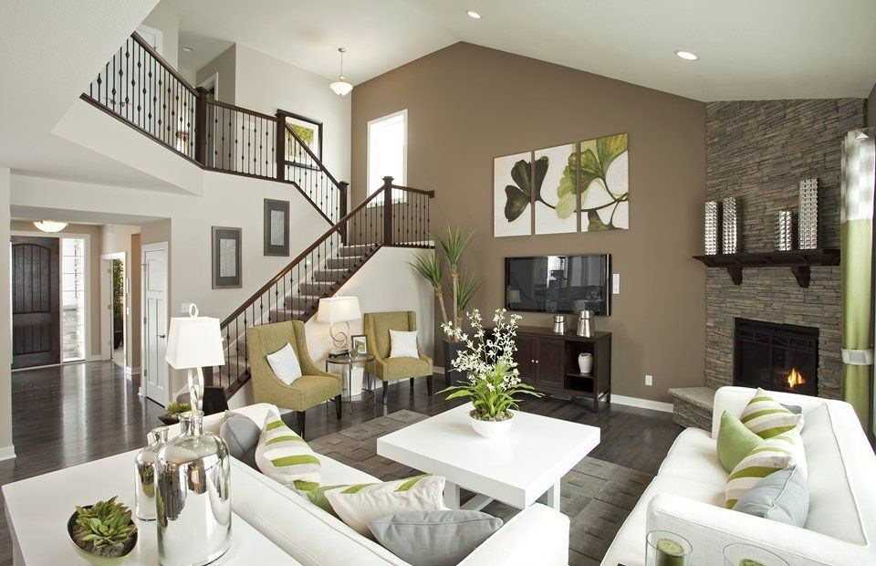 Olive and other shades of green visible in this living room showcase a love of nature, while the white furniture (like the center table, display rack and sofa set) represents purity and neatness in this design.