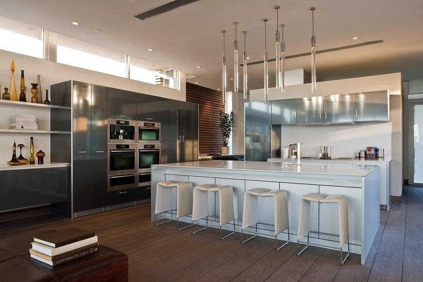 Modern kitchen design with several wall ovens mounted in a wall pantry that is easily accessible from the main kitchen area.