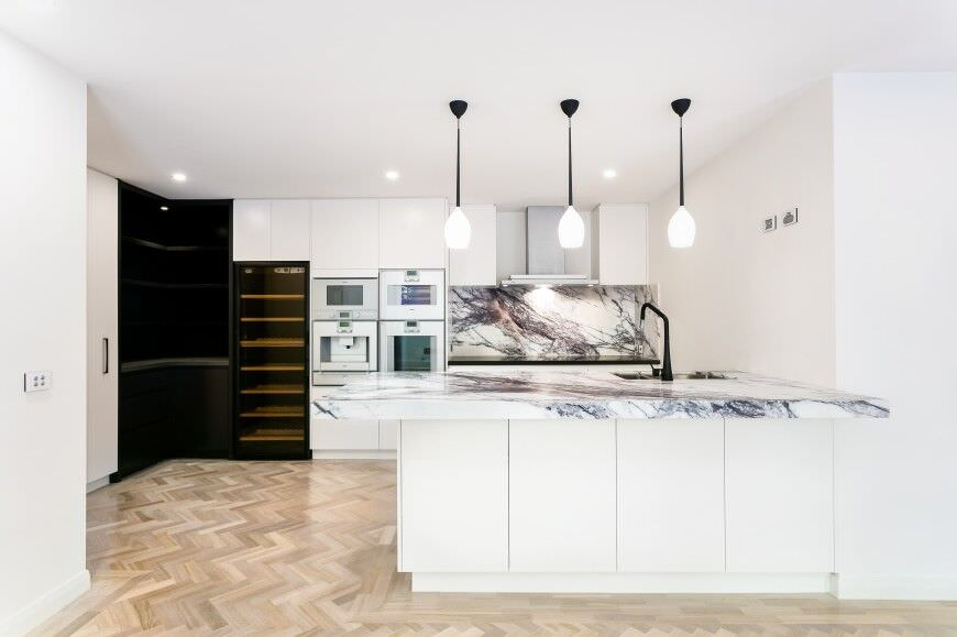 Contemporary kitchen design with a double wall oven located in the heart of the kitchen for convenient use.