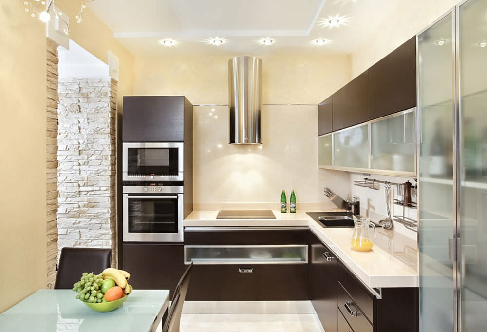 Modern small kitchen design with dark cabinetry, light countertops and double wall oven.
