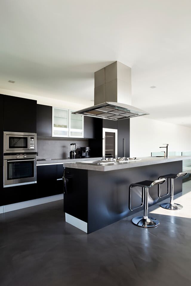 Black modern kitchen with single wall oven and microwave above.