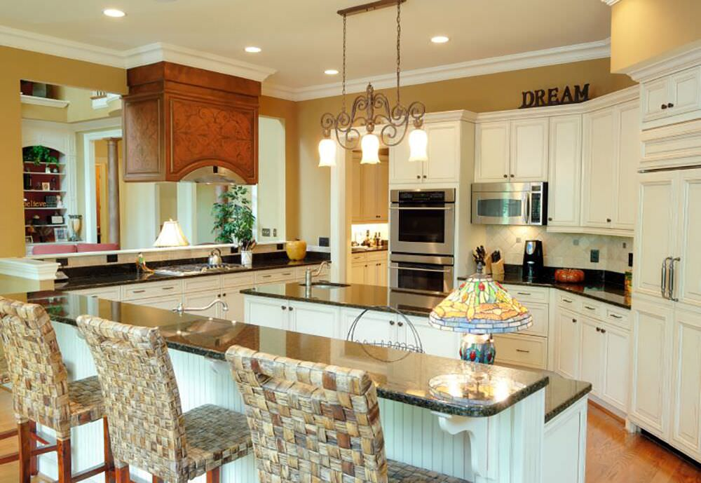Stunning white kitchen with 2-tiered breakfast bar in a large pie-shape.