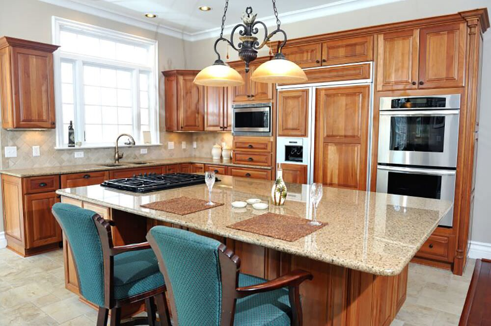 Traditional kitchen design with wood-paneled fridge and and double wall oven.