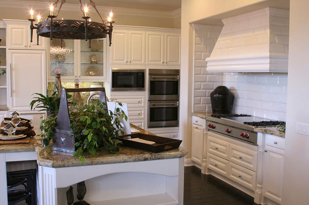 Stylish white kitchen with fabulous subway tile backsplash and double wall oven.