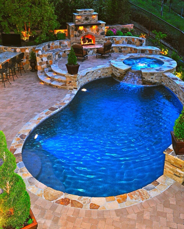 Here's a bright royal blue swimming pool with hot tub and massive multi-level brick patio. Patio includes large wood-burning fireplace and dining area.