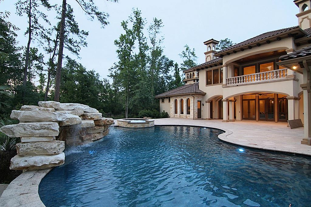 Mediterranean style mansion with large kindey shaped pool and adjacent hot tub.