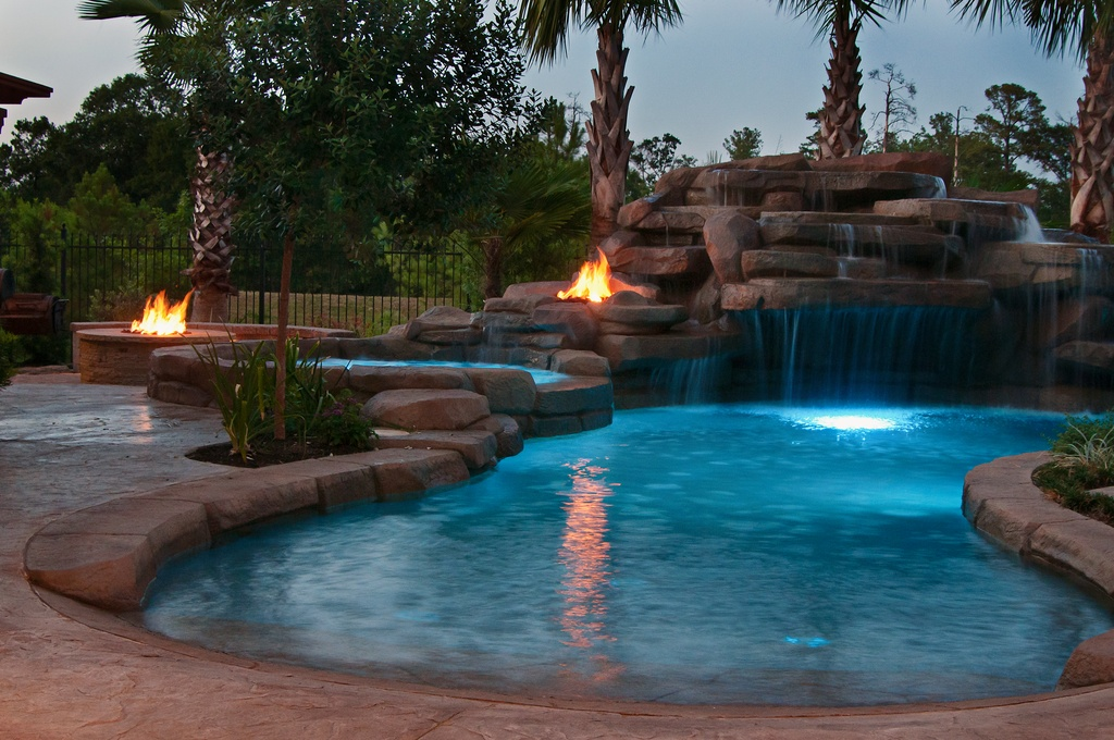 Dramatic kidney pool at night surrounded by 2 firepits.  This also has a cave with waterfall entry.  This is a great pool area.
