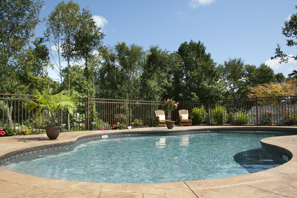 Here's a nice-looking kidney shaped pool with light-brown flagstone patio with a wrap-around safety fence.