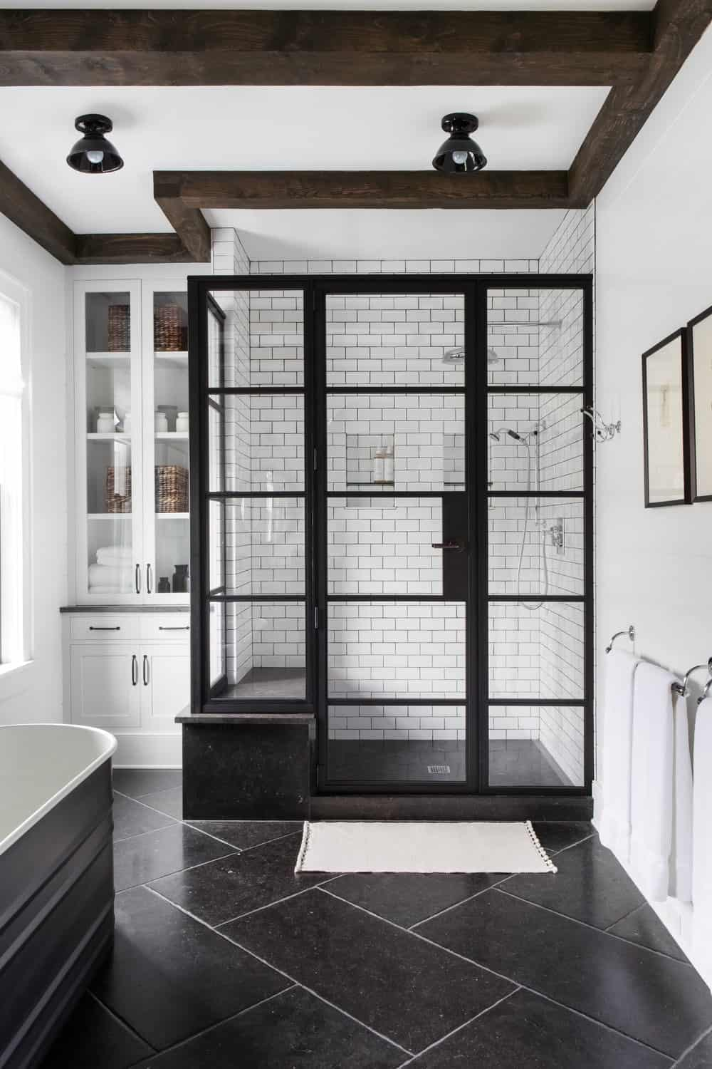 This charming bathroom has a glass-enclosed shower area that has black frames matching the black flooring tiles that contrast the white walls and white ceiling. This is adorned with a wooden beams and a pair of black semi-flush mount lights.