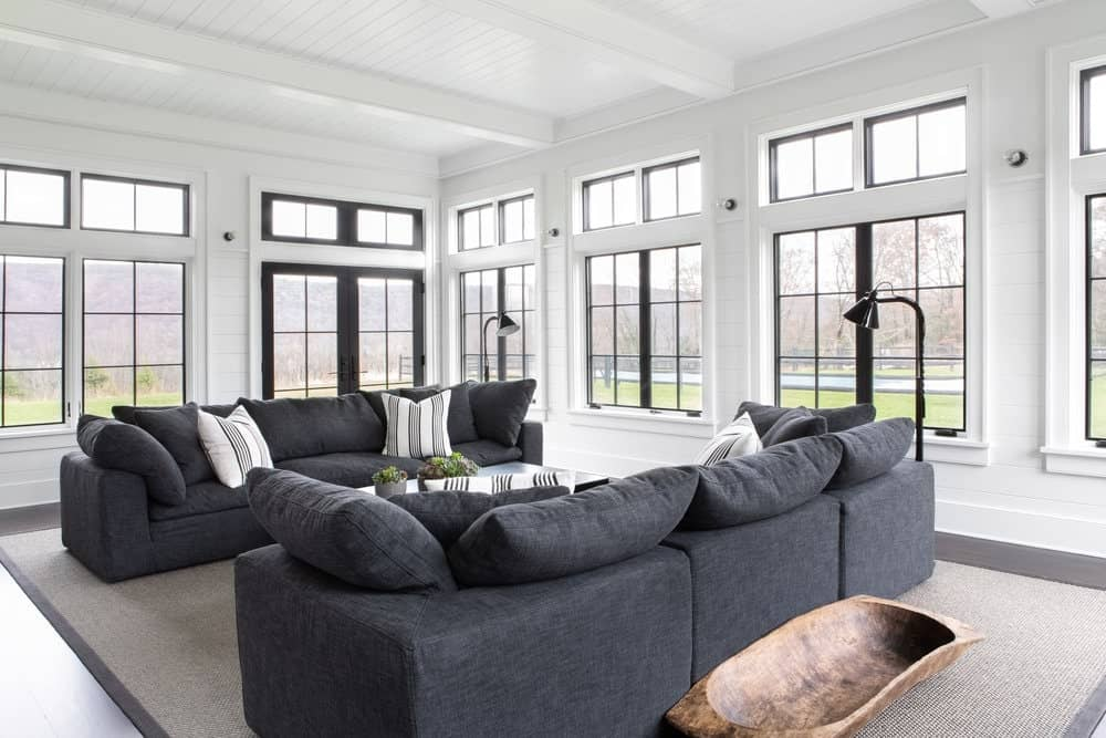 This is a bright living room with white wooden ceiling that has white exposed wooden beams matching with the white walls that bring in an abundance of natural lighting through the surrounding tall windows that lighten up the gray comfortable sofas.