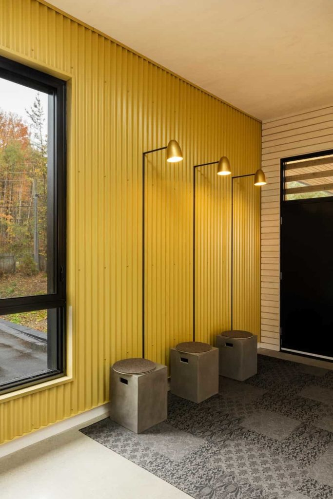 This simple Industrial-style entry hall has a gray patterned area rug on its off white flooring. This is brightened by the delightful yellow hue of the walls made of metal and the wall-mounted lamps attached to it over three small built-in concrete stools.