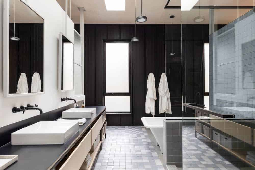 This modern industrial-style bathroom has gray flooring tiles that complement the black wall with a frosted glass window on the far end that matches with the countertop of the two-sink vanity with matching black fixtures.