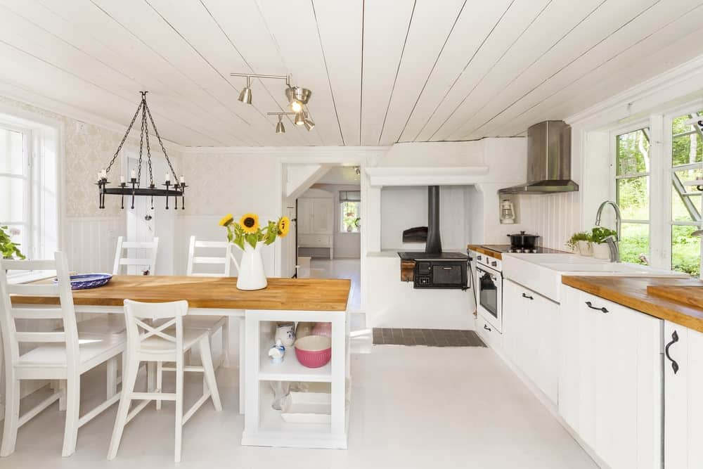 This is a bright and predominantly white dining area inside the kitchen with the same white shiplap ceiling and white flooring. The brightness is subdued by the wooden tabletop of the dining table and the black farmhouse-style chandelier hanging above it.