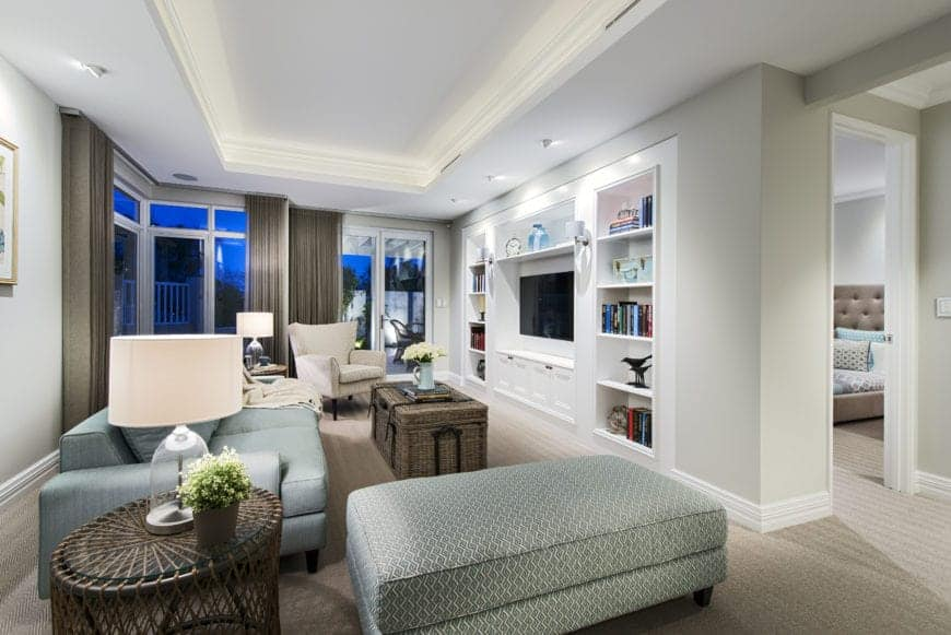 The white tray ceiling of this living  room has brilliant recessed lights that brighten up the white wooden structure built into the wall. This structure has shelves, cabinets and houses the TV that is enjoyed by those sitting on the green patterned sofa.