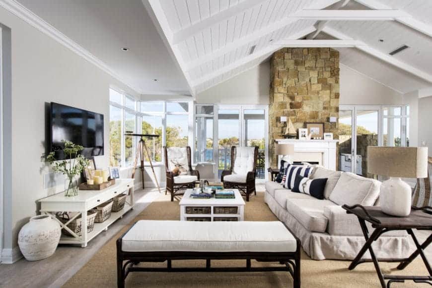 This is a large inviting living room that treats its guests with a bright comfort. It has a high white cathedral ceiling with exposed beams matching the window frames that bring in natural lights to the large beige sofa over a woven area rug.