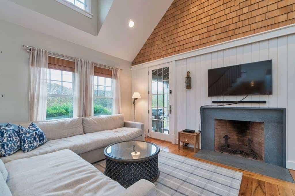 This small and cozy Farmhouse-style living room is brightened by the natural lights coming from the windows and glass door that feature a green landscape outside. This lightens up the gray sectional sofa and the fireplace inlaid with dark gray marble.