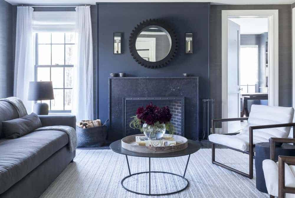 This living room has dark gray walls that is counterbalanced by the brightness of the windows and door flanking the fireplace that has a dark gray mantle blending with the wall adorned with a round mirror mounted above it. This is a nice background for the gray sofa and its circular coffee table.