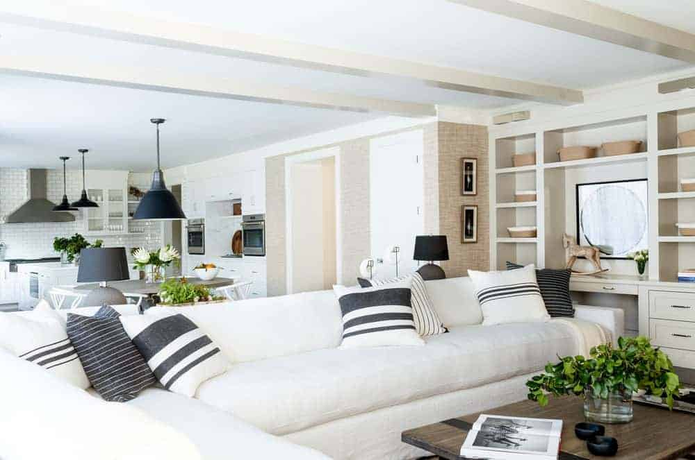The large L-shaped sectional beige sofa dominates this small living room area beside the dining area. The inviting comfort of the sofa is perfectly paired with a rustic and homey wooden coffee table and a white ceiling that has exposed wooden beams.