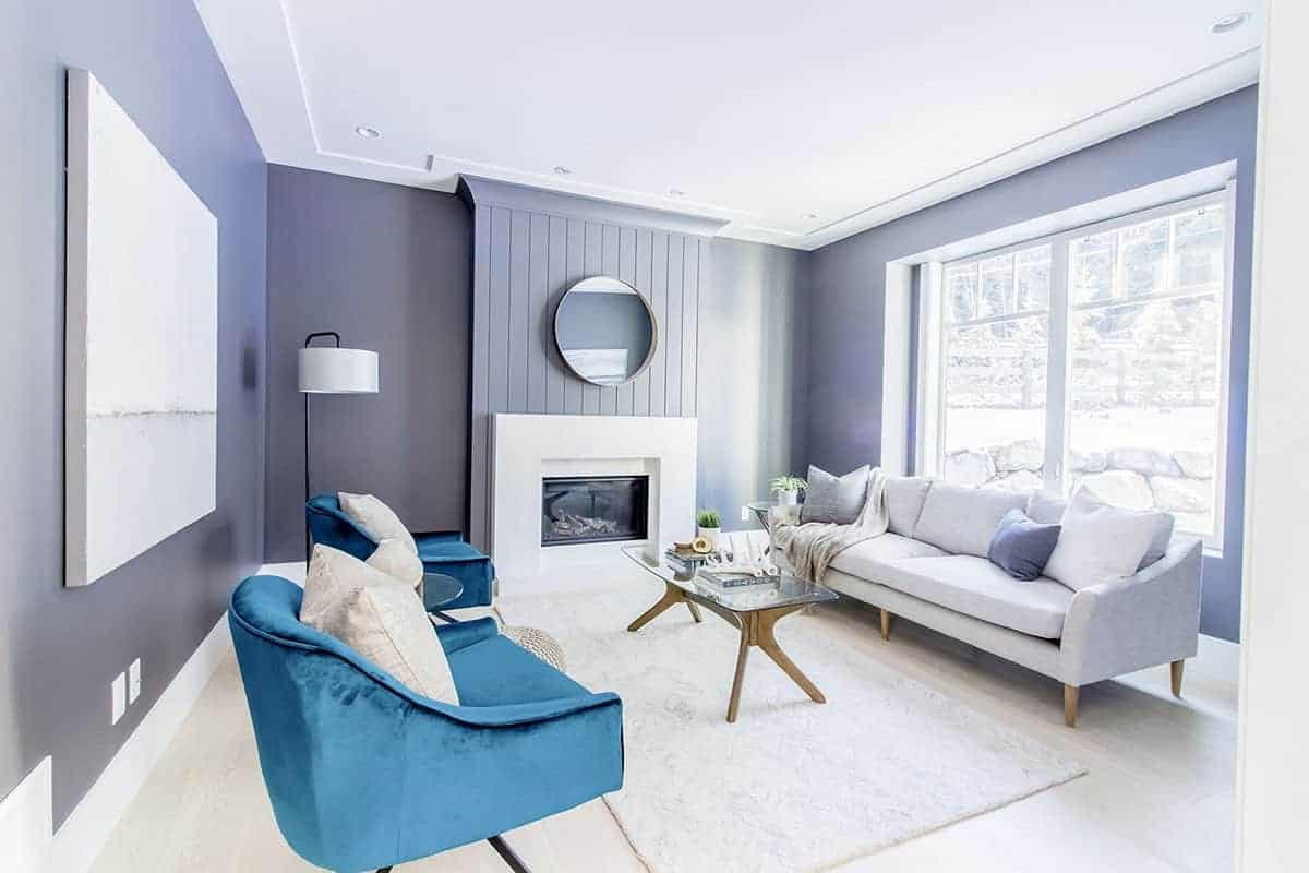 The bright windows behind the light gray couch brings in an abundance of natural lights to the gray walls of this living room. This complements the blue velvet cushioned chairs that stand out against the light hardwood flooring blending with the mantle of the fireplace.