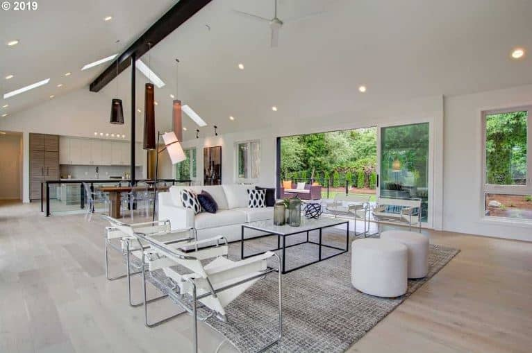 The white cathedral ceiling has a single contrasting exposed wooden beam right on the middle that supports the white ceiling fan. This matches with the white sofa, white modern armchairs and the two white round ottomans that stand out against the gray area rug.