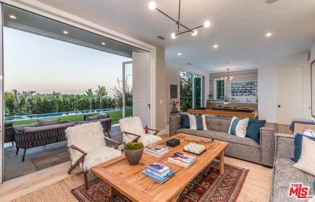 A wonderful view of the backyard pool provides a nice background for the living room that has a light hardwood flooring topped with a colorful patterned area rug under the wooden coffee table that is surrounded by a couple of gray sofas and a couple of wooden armchairs with furry cushions.