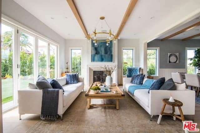 The white ceiling that has a couple of exposed wooden beams hangs a circular farmhouse-style golden chandelier over the wooden coffee table that is flanked by the two long sofas with green pillows that match the green painting above the fireplace.