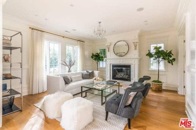 This bright living room has a hardwood flooring that is covered by a light gray patterned area rug. This complements the white cushioned sofa and the pair of cushioned tufted gray chairs across from it beside a couple of white furry ottomans.