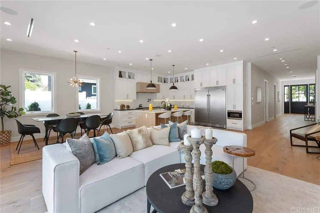 This living room is part of a great room that also houses the dining area and the kitchen all under one large white ceiling with recessed lights. This brightens up the white cushioned sectional sofa with colorful pillows. This dofa is paired with a black coffee table and a light gray area rug.