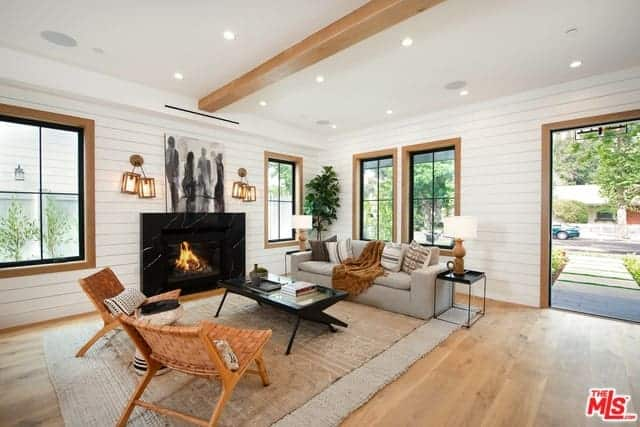 As you enter this home, you will see the living room area on the right side of the hardwood flooring that is marked with a large rustic woven area rug that matches with the light gray sofa facing a black coffee table that pairs well with the black fireplace.