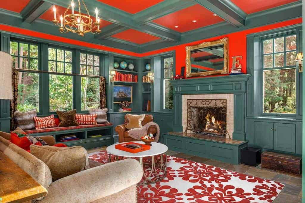 This living room is dominated by the deep green hue of the coffered ceiling and wall finish that is surrounded by windows. The second dominating hue of this living room is the bold orange that can be seen in between the green elements.