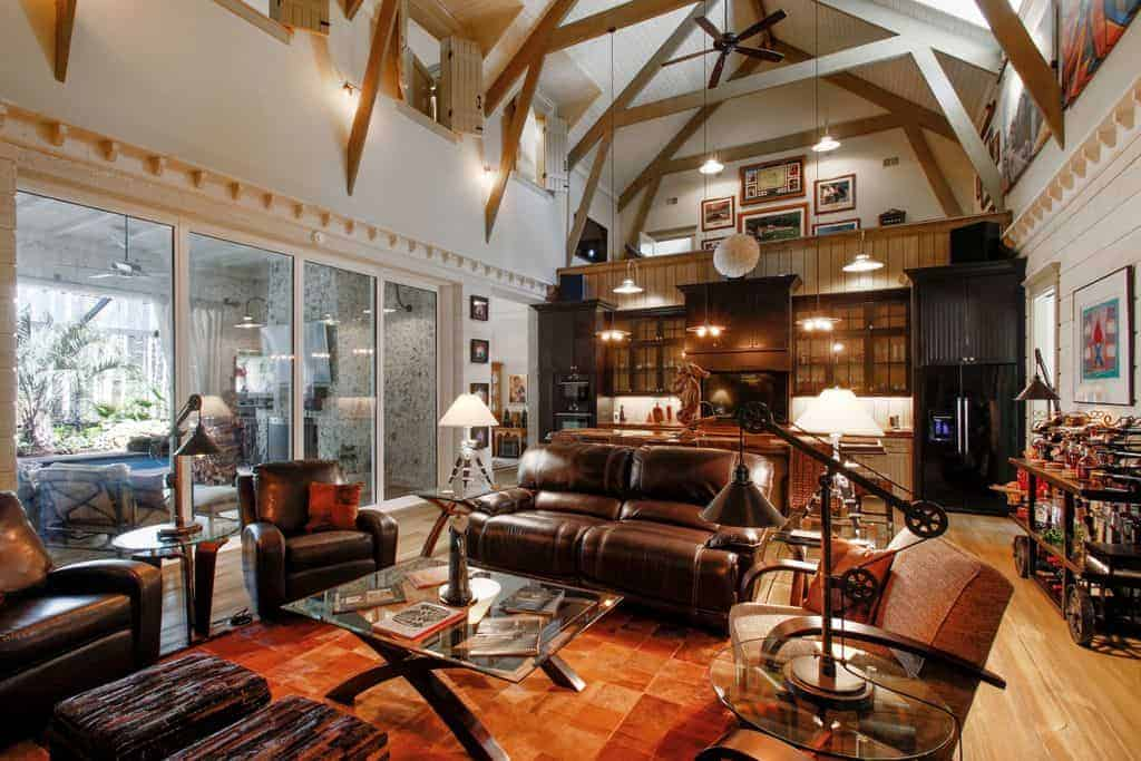 This living room area is part of a large room with a high cathedral ceiling that also houses the kitchen on the far side. The living room has brown leather cushioned sofas and armchairs that complement the rust-colored area rug underneath the glass-top coffee table.