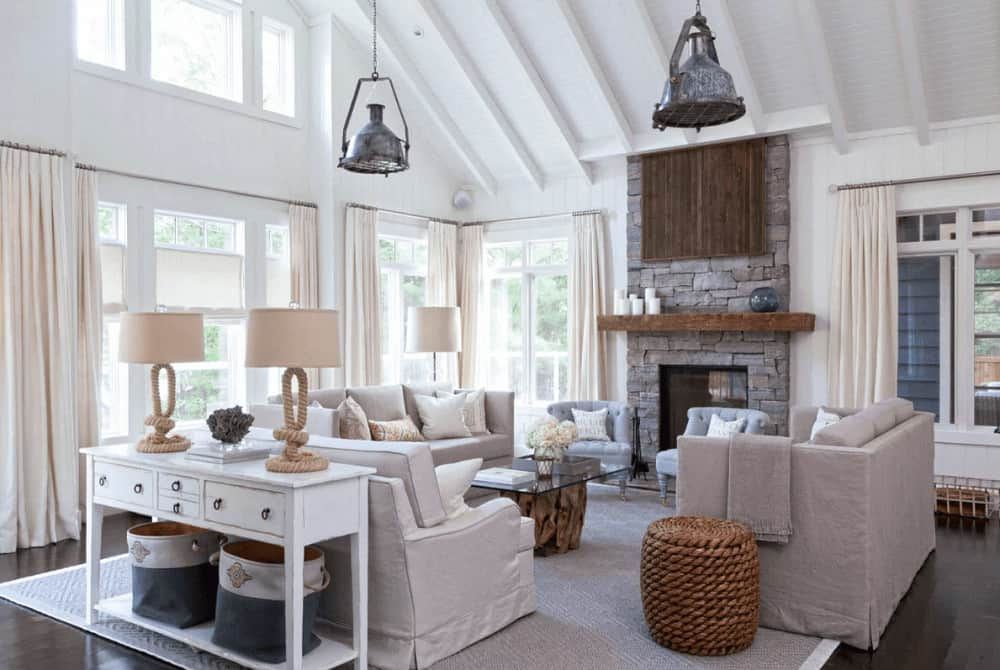Chrome dome pendants illuminate this living room boasting skirted sofas and a glass top coffee table facing the gray tufted chairs and a brick fireplace that's lined with a wooden mantel.