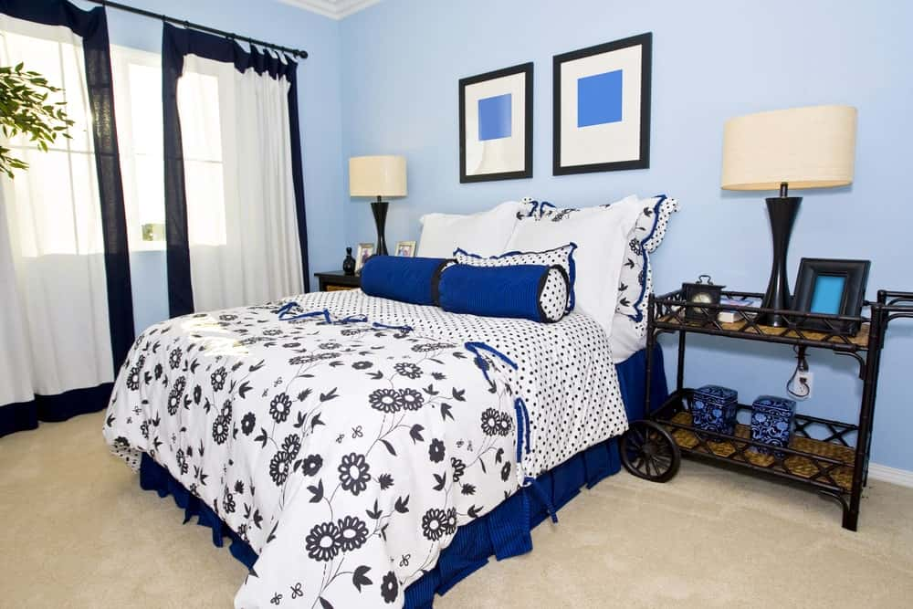 Sleek drum table lamps sit on black nightstands flanking a blue skirted bed dressed in dotted and floral bedding. It is accented with framed wall arts mounted on the light blue wall.