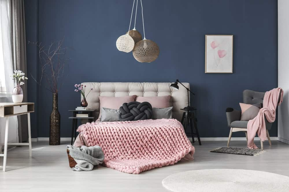 Navy blue bedroom accented with light pink bedding, artwork and throw blanket that lays on the green tufted armchair. It is decorated with lovely flower vases and boho pendant lights that hung over the gorgeous bed.