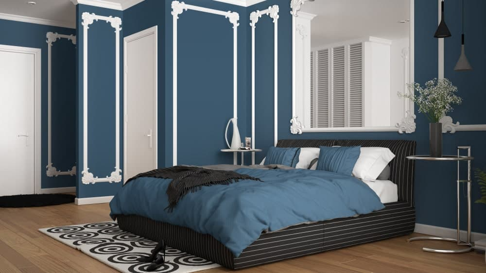 Classy master bedroom designed with ornate wainscoting and a matching mirror that hung above the black striped bed flanked by round side tables.