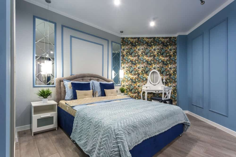 An eye-catching floral wallpaper clad on the corner wall sets a gorgeous backdrop to the white vanity in this blue bedroom with a velvet tufted bed and white nightstands paired with stylish rectangular mirrors.