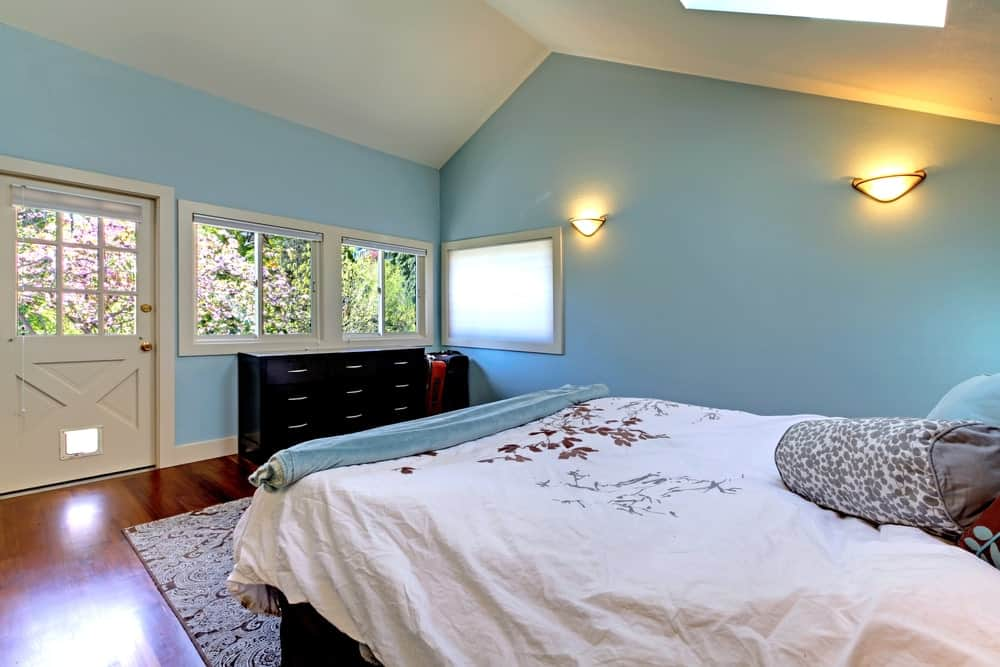 This bedroom boasts dark wood dresser and a comfy bed lighted by glass sconces that are mounted on the sky blue wall. It has a vaulted ceiling and rich hardwood flooring topped by a patterned area rug.