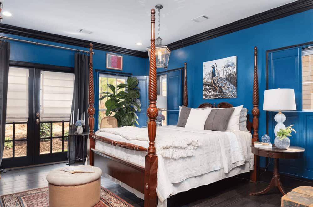 Classic blue bedroom decorated with a lovely peacock artwork and lantern pendant light that hung over the four poster bed accompanied by white table lamps and round ottoman.