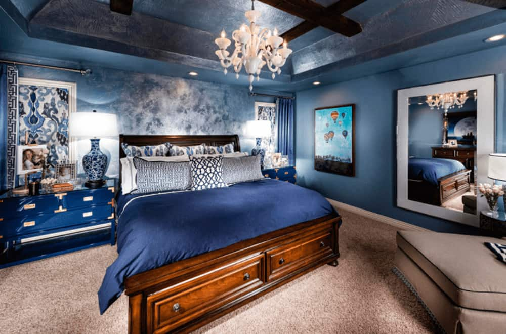 A gorgeous white chandelier illuminates this master bedroom boasting a wooden bed and ceramic table lamps that sit on the blue nightstands.