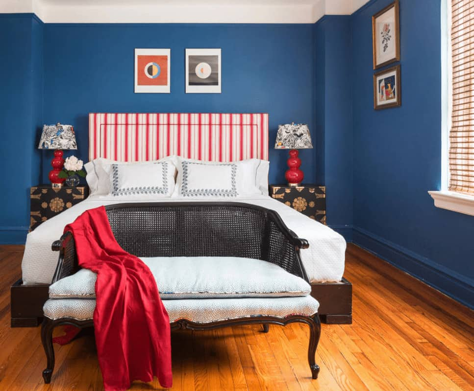 A wicker cushioned bench sits in front of the wooden bed with red striped headboard flanked by charming table lamps and floral nightstands.