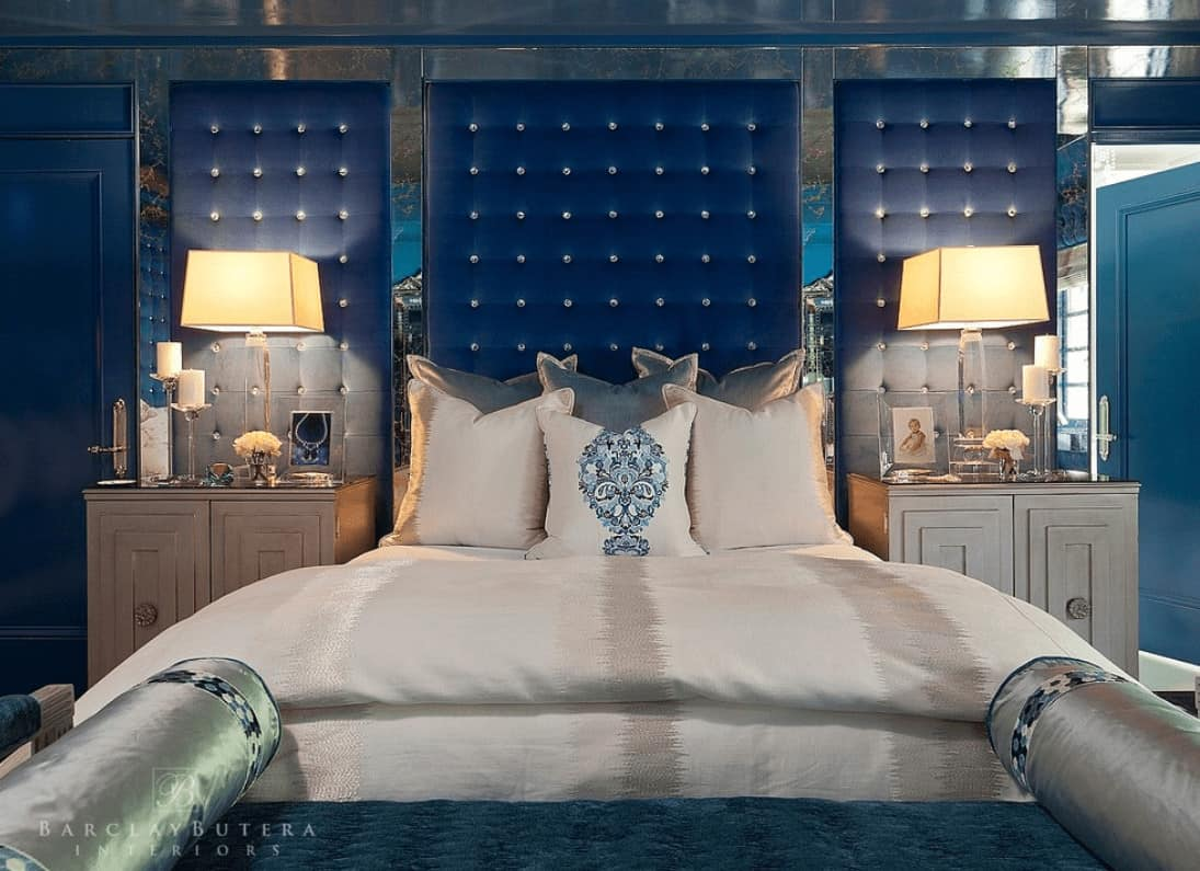 Luxury master bedroom with a classy bed and wooden nightstands placed against the mirrored wall that's fitted with blue tufted panels.