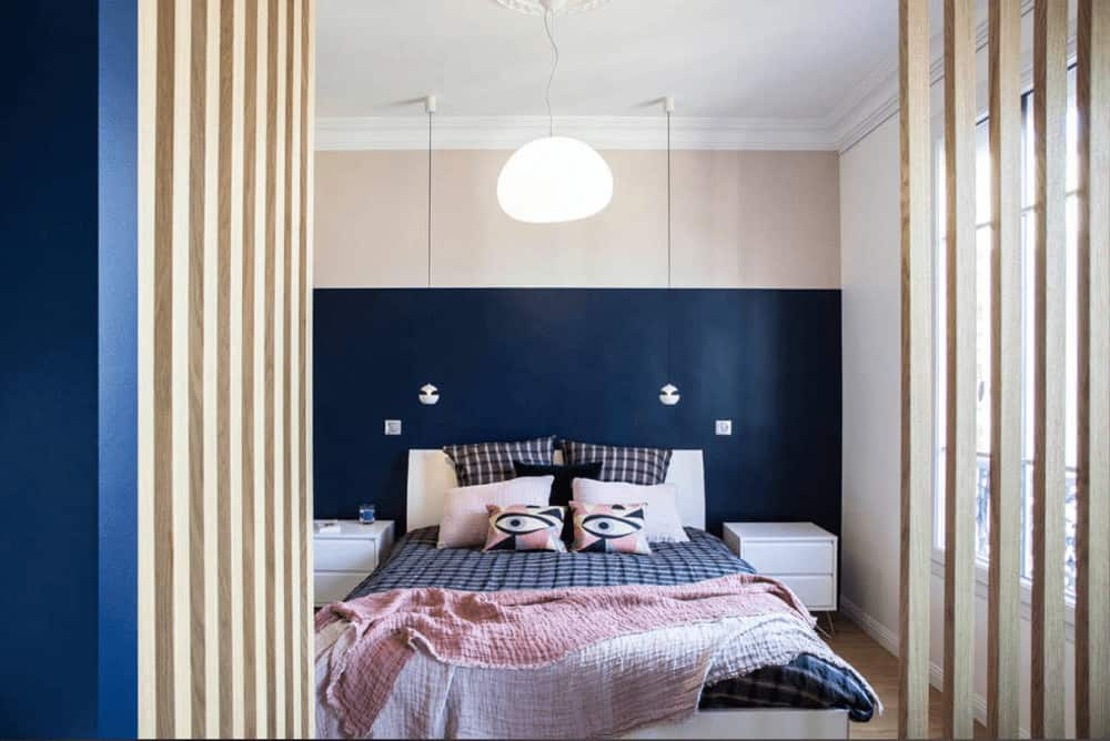 A wooden slat door opens this cozy bedroom with white nightstands and sleek bed illuminated by glass and mini pendant lights.