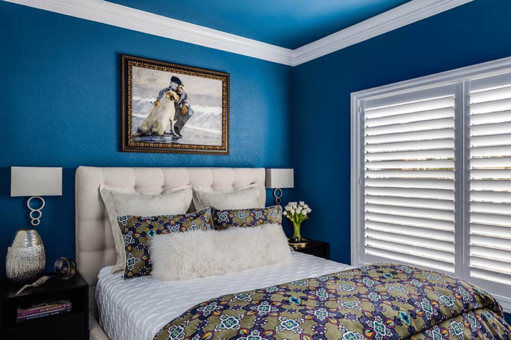 A closeup look at this blue bedroom showcasing sleek sconces above dark wood nightstands and beige tufted bed with a gorgeous painting on top.
