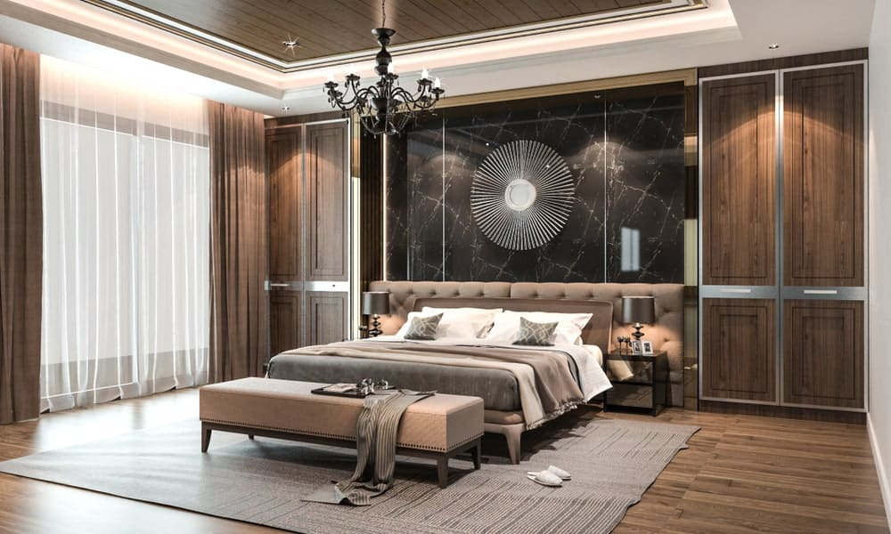 Classy master bedroom boasts a wrought iron chandelier and sunburst decor mounted on the black marble wall. It has a cozy bed with custom tufted headboards placed in between built-in cabinets.