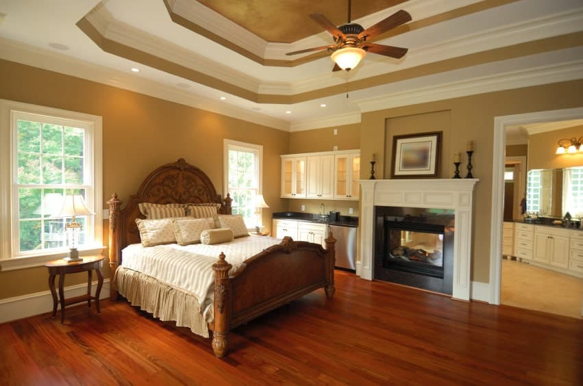 Classic brown master bedroom offers a fireplace and carved wood bed illuminated by flush and recessed lights mounted on the double tray ceiling.