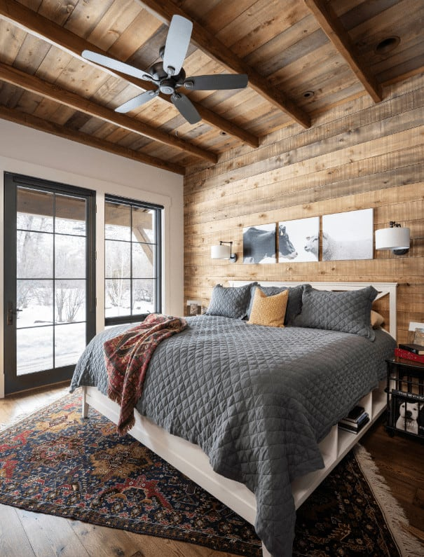 Cozy master bedroom with multi-panel wall art and white bed on a tasseled rug wrapped in a gray quilt. It has black framed windows and wood plank ceiling mounted with a fan.