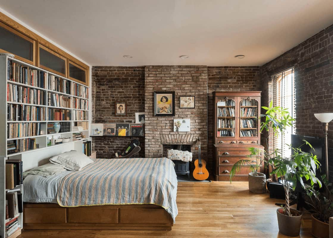Green potted plants create a refreshing ambiance in this master bedroom showcasing built-in bookshelves and a fireplace concealed in the brick walls.