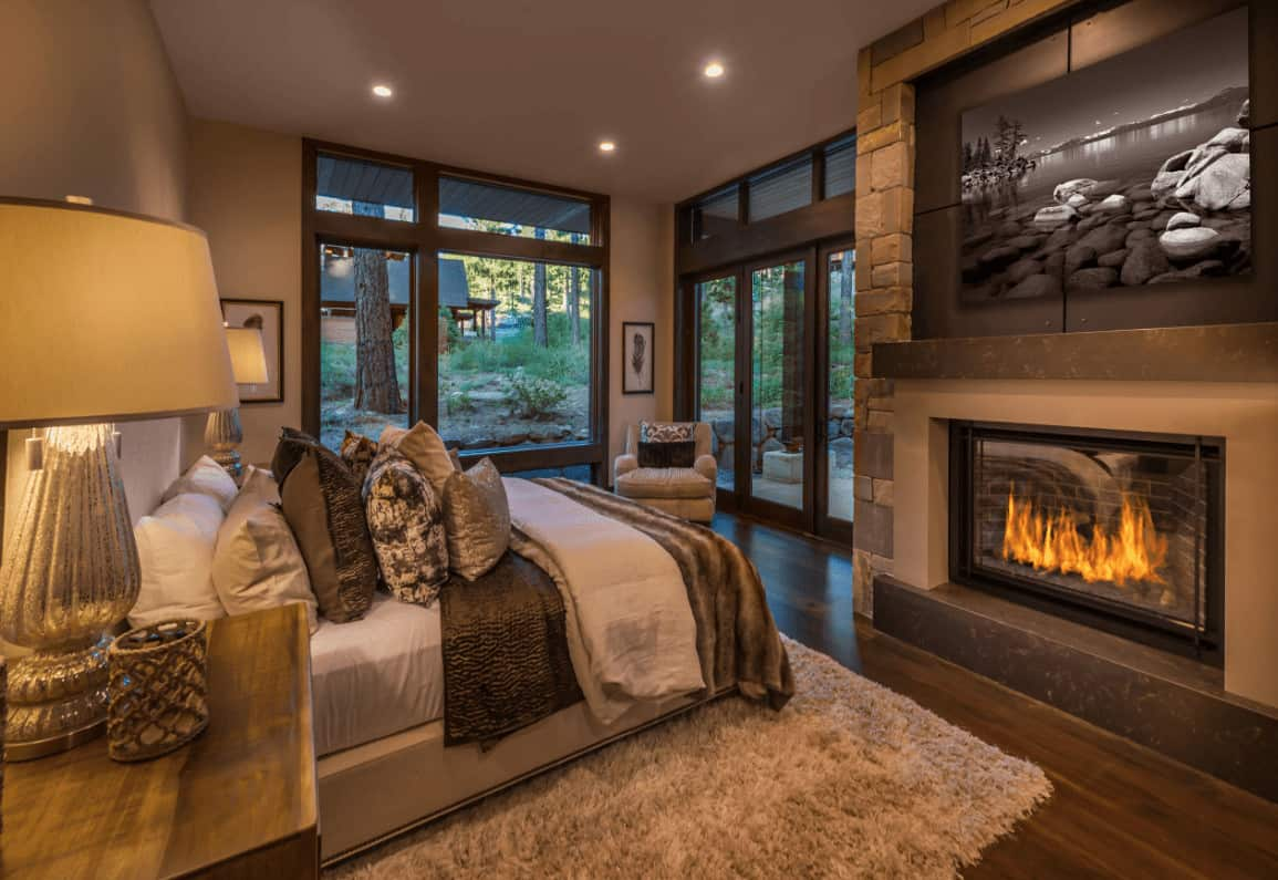 The warm master bedroom boasts a comfy bed and a fireplace with a landscape canvas on top. It has full height glazing and hardwood flooring topped by a gray shaggy rug.