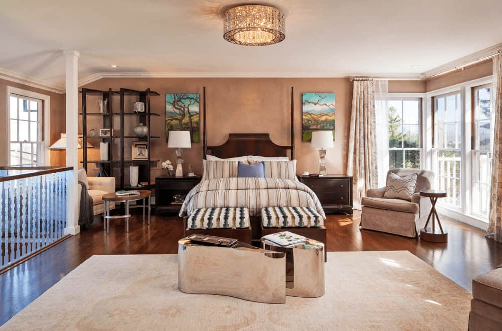 This master bedroom is decorated with a fancy flush mount light and lovely tree wall arts that hung over the dark wood nightstands. It has beige seats and a wooden bed with striped ottoman and stylish mirrored tables on its end.